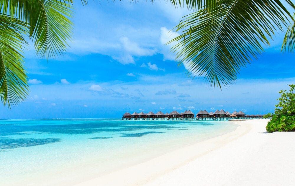 Písečná pláž a chýšemi v pozadí