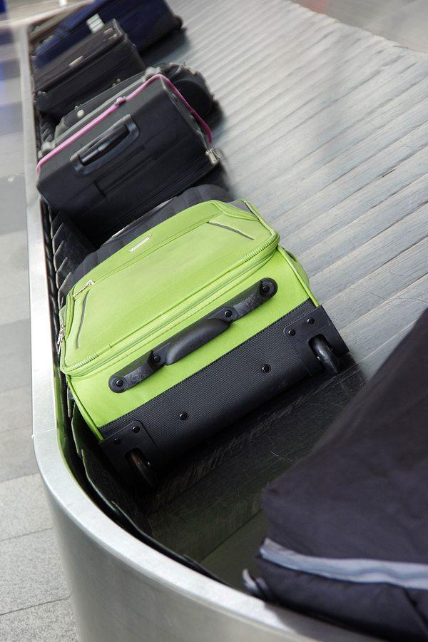 zavazadlový pás se zeleným kufrem
