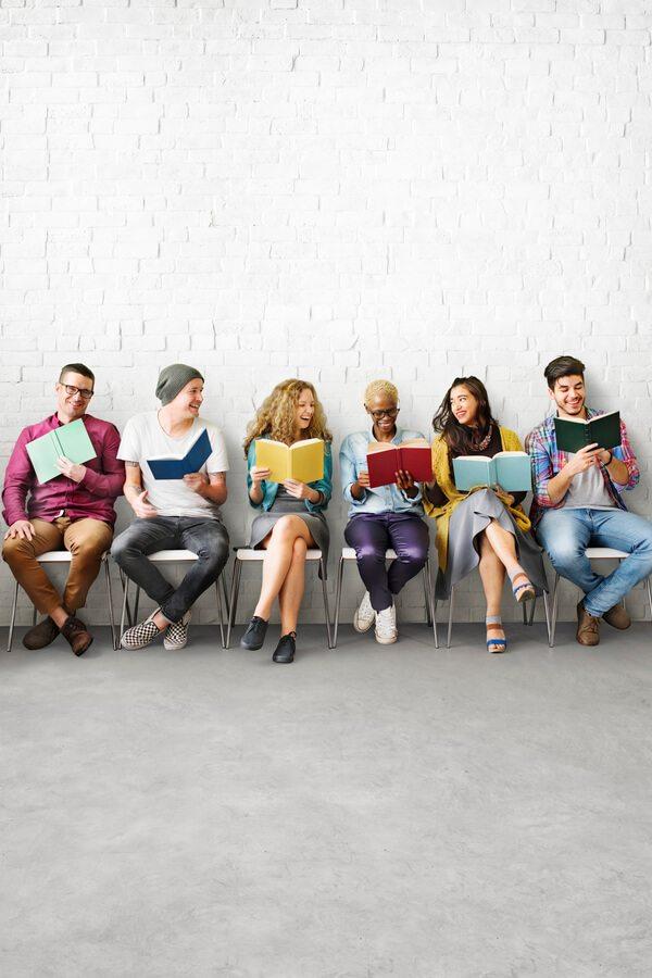 Lidé s knihou sedící na lavičce.
