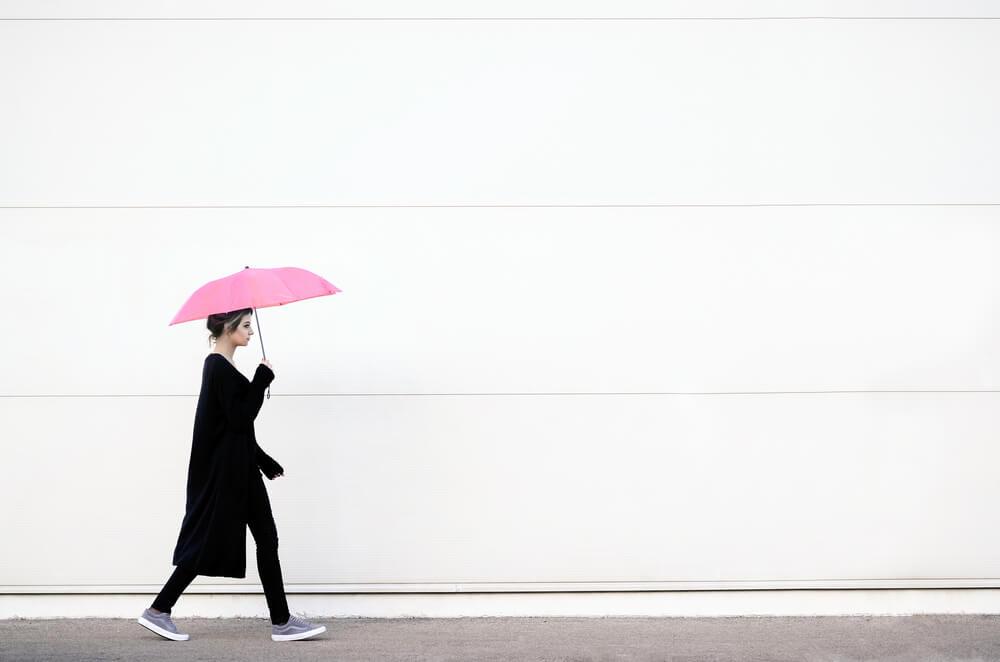 Žena jdoucí po ulici s deštníkem v ruce.