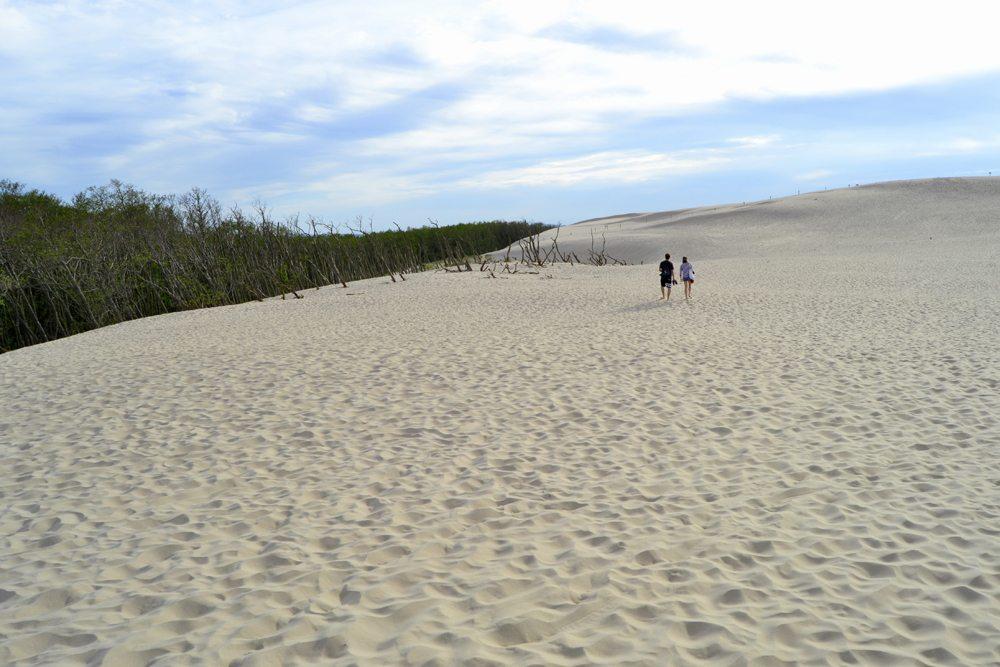Pár procházející se po písečných dunách na severu Polska.