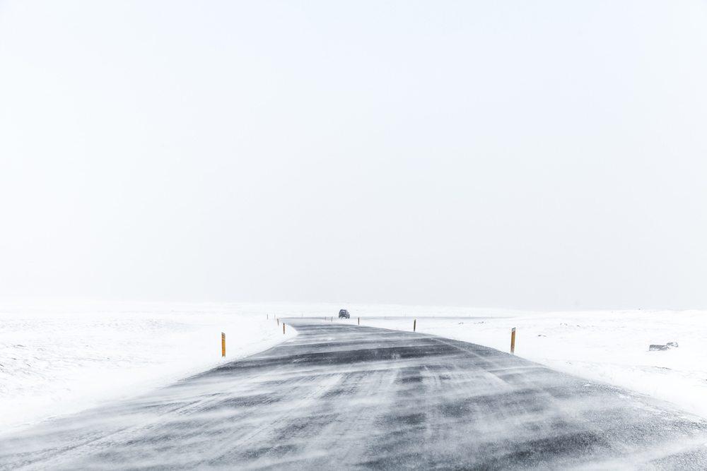 Prázdná zasněžená cesta na Islandu.