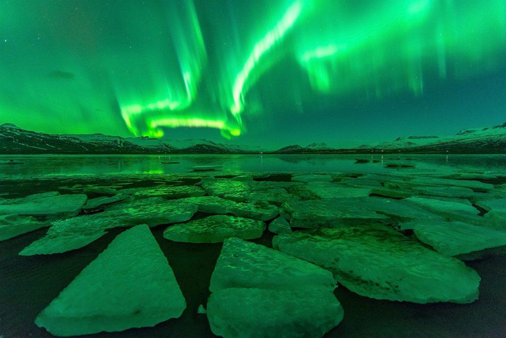Polární záře nad jezerem, Island.