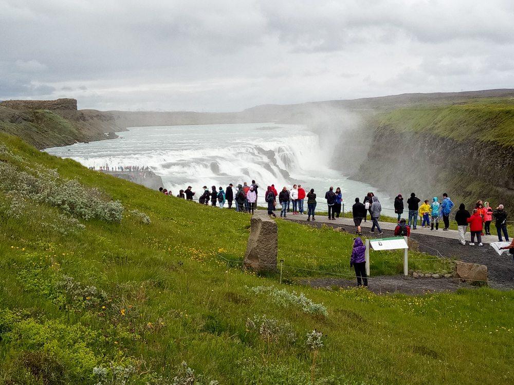 Dav turistů u vodopádů, Island.