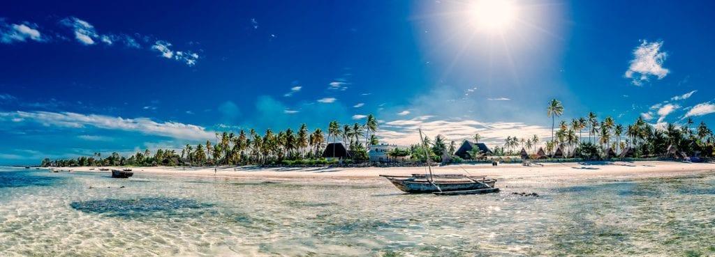 Vody Zanzibaru s loďkou a pláží v pozadí