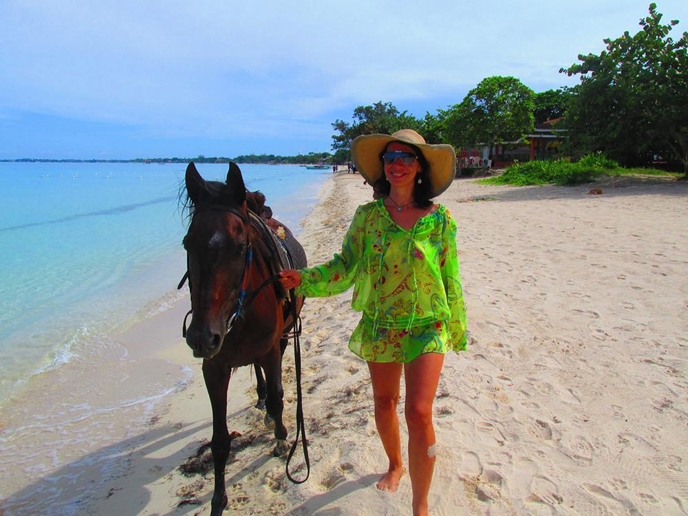 Nita s koněm na pláži.