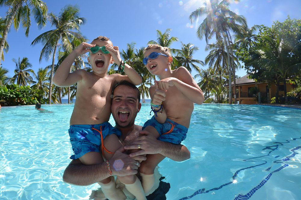Chlapci s otcem v bazénu.