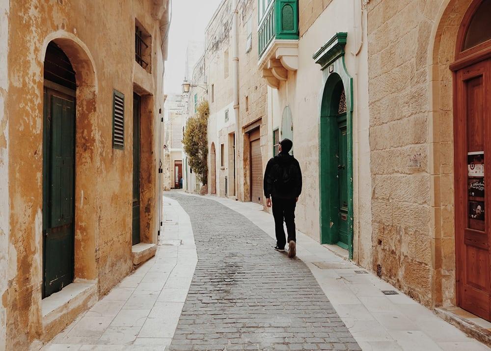 Muž procházející po uzkých uličkách na Maltě.