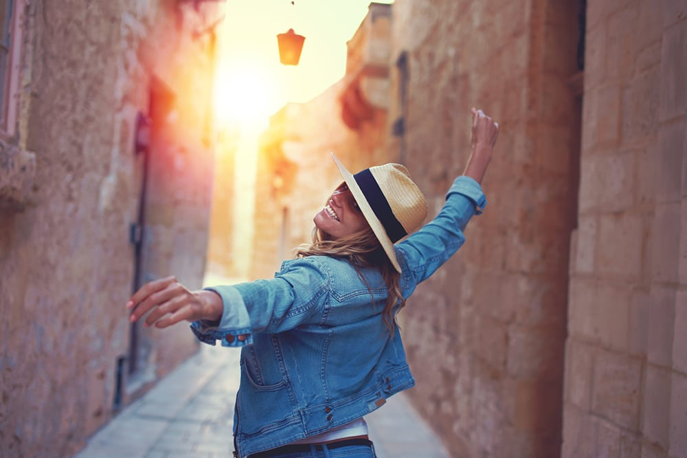 Šťastná žena v klobouku procházející se uličkami na Maltě.