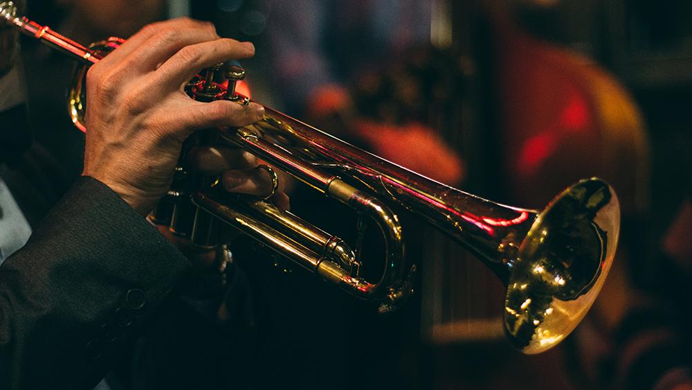 Hudebník hrající na trubku.