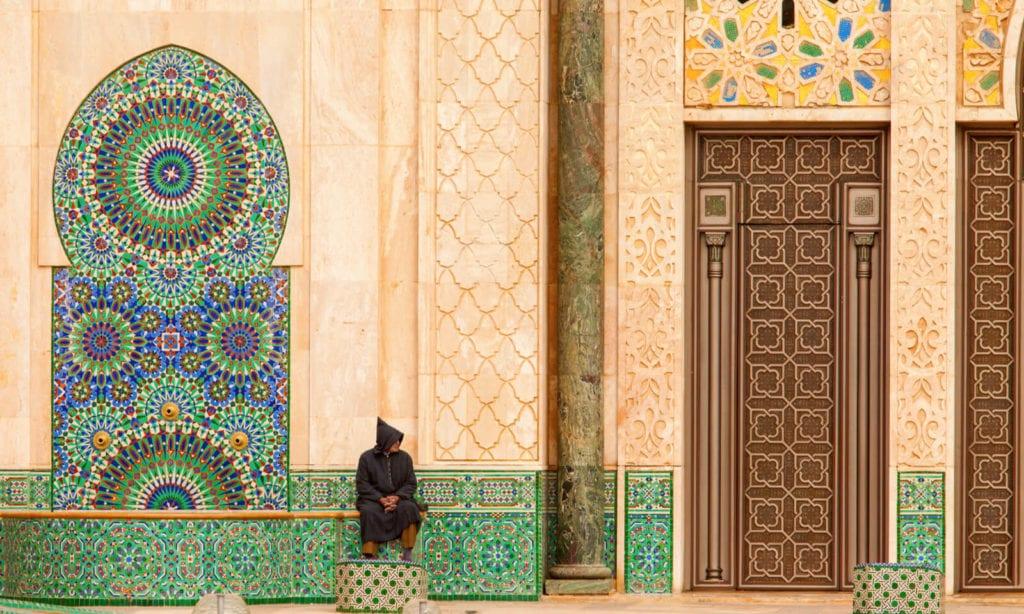 Muž sedící před zdobenými dvěřmi mešity v Casablance.